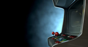 Arcade Machine Dramatic View. A vintage unbranded arcade game with a joysticks and buttons and a blank screen on a dark ominous background with copy space Royalty Free Stock Photography