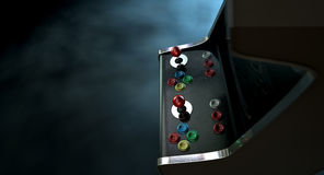 Arcade Machine Dramatic View. A vintage unbranded arcade game with a joysticks and buttons and a blank screen on a dark ominous background with copy space Stock Photos
