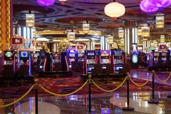 Arcade machines and gamblers inside casino in Macau. MACAU, CHINA- 06 APR, 2018: Arcade machines and gamblers inside casino in Macau Stock Image