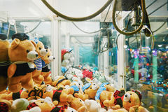 Arcade robotic claw game machine. Claws with soft plush toys in an arcade machine Stock Photos