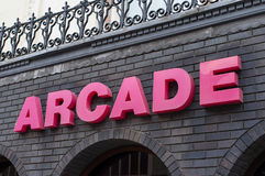 Arcade. An arcade sign in pink lettering on a brick wall background Stock Photos