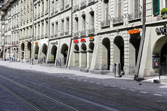 Arcades in historic buildings in Bern. Bern, Switzerland - April 17, 2017: Arcades in historic buildings along the street are the pride of the old town. Tram Royalty Free Stock Image