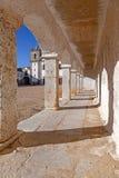 The arcades of the pilgrim lodgings in the Baroque Sanctuary of Nossa Senhora do Cabo. Aka Nossa Senhora da Pedra Mua in Espichel Cape and the church at the Stock Images
