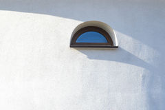 Arced window on wall. Latticed window in arches shape at white medieval church wall Stock Photo
