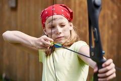 Arcere della ragazza con l'arco che spara allo scopo di sport Fotografia Stock