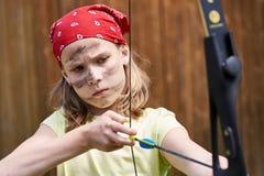 Arcere della ragazza con l'arco che spara allo scopo di sport Fotografia Stock Libera da Diritti