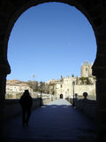 Arch 01. This stone arch is found in Spain. It was photographed as a siloutte so the focus is on the town past it Royalty Free Stock Photography