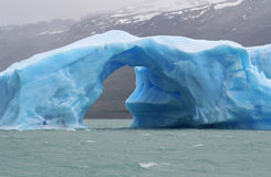 The arch. Iceberg with an arch of ice floating in argentino lake, in the argentinian national park of glaciers Stock Images