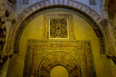 Arch above the Arabic inscriptions on a wall inside the Mezquita. Arabic inscriptions on a wall inside the Mezquita,Mezquita de Córdoba,the Great Mosque of Có Stock Photography