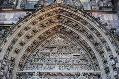 Arch above main doors at Romanesque Church in Thann, France. This church are reminiscent of Winchester Cathedral in England. The stone-work here is incredibly Stock Photos