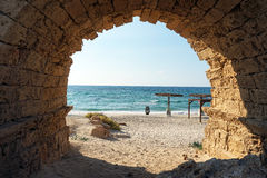 Arch of aqueduct. Entrance to the sand beach through the arch of aqueduct near Caesarea, Israekl Royalty Free Stock Image