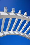 Arch of arbor. Low angle view of arched white trellis with blue sky Stock Photos