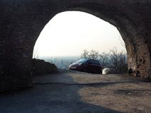 Arch architecture car. The old architecture of the arch behind which the car rides Stock Image
