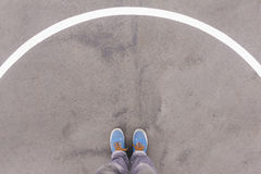 Arch on asphalt ground, feet and shoes on floor Stock Image