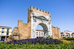 Arch of Augustus in the modern urban Context - Rimini, Italy. Bright perspective view of the Arch of Augustus in the modern urban context of Rimini in Italy Stock Photo