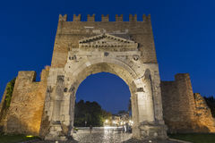 Arch of Augustus at night in Rimini, Italy. Ancient romanesque gate of the city - historical landmark, the most ancient roman arch that still stands intact Stock Photo