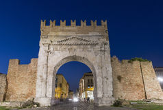 Arch of Augustus at night in Rimini, Italy. Ancient romanesque gate of the city - historical landmark, the most ancient roman arch that still stands intact Stock Photos