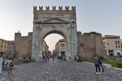 Arch of Augustus in Rimini, Italy. People in front of Arch of Augustus, ancient romanesque gate of the city - historical Italian landmark, the most ancient Royalty Free Stock Image