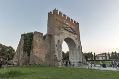 Arch of Augustus in Rimini, Italy. People walk in front of Arch of Augustus, ancient romanesque gate of the city - historical Italian landmark, the most ancient Stock Images