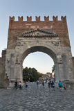 Arch of Augustus in Rimini, Italy. People walk in front of Arch of Augustus, ancient romanesque gate of the city - historical Italian landmark, the most ancient Stock Photo