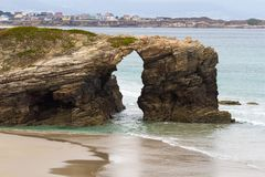 Arch on the Beach of the Cathedrals an and Town of Foz stock photography