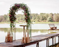 Arch. Beautifully decorated wedding arch with fresh flowers on the lake Stock Photos