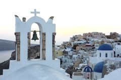Arch with a bell, white houses and church with blue domes in Oia or Ia at golden sunset, island Santorini, Greece. - Immagine royalty free stock photography