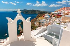 Picturesque view of Oia, Santorini, Greece. Arch with a bell, white houses and church with blue domes in Oia or Ia, island Santorini, Greece Stock Images
