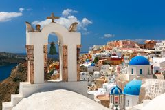 Picturesque view of Oia, Santorini, Greece. Arch with a bell, white houses and church with blue domes in Oia or Ia, island Santorini, Greece Stock Photo