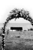 Arch with Bench. Flowered arch with a bench. Set up for a wedding on the shore. Black and white. Comments welcome Stock Images