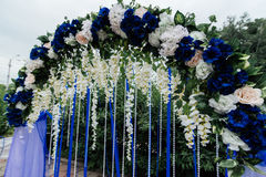 Arch with blue, white flowers, greenery and blue ribbons. Wedding arch with blue, white flowers, greenery and blue ribbons Royalty Free Stock Image