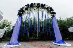 Arch with blue, white flowers, greenery and blue ribbons. Wedding arch with blue, white flowers, greenery and blue ribbons Stock Photos