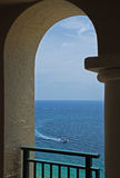 Arch, Boat and Ocean. An inviting view of a boat on the ocean through an arch of a balcony Royalty Free Stock Photography