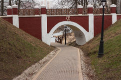 Arch brick footbridge. With wooden railing in the city park and footpath beneath Stock Images