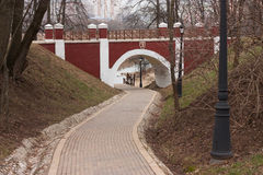 Arch brick footbridge. With wooden railing in the city park and footpath beneath Royalty Free Stock Photos
