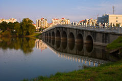 Arch bridge across a lake Stock Photo