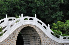 Arch bridge in garden. Part of white arch bridge with green tree background in garden, shown as color and shape, quiet environment and oriental style Royalty Free Stock Image