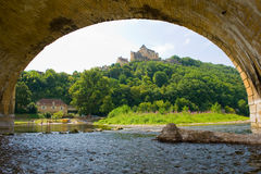 Arch of bridge. Arch of the bridge of Grolejac over the river Dordogne in France with a chateau on the mountain Royalty Free Stock Photos