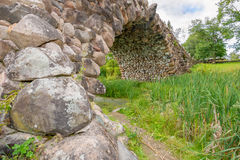 Arch bridge. Hundred-meter boulder-arch bridge with two grotto - aviary, called by locals Devil's Bridge. Consisting of dry stacked boulders, kept only by Stock Image