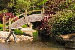 Arch Bridge in a Japanese Style Garden. Arch wooden over a pond at a Japanese style botanical garden in Missouri Stock Photos