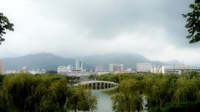 Arch bridge on lake in willows Park.City rely on distant hills. Gh2_02788 stock footage
