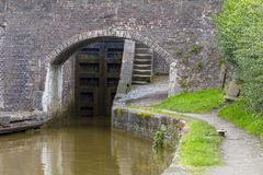 Canal lock with arch bridge in Cheshire UK. Arch bridge with lock and towpath steps in the Cheshire countryside Stock Photography