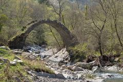 The arch bridge in mountains, Alps, Italy. Ruins of arch bridge in mountains, Rezzo municipality, Province of Imperia, Italy Stock Photos