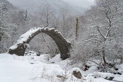 Arch bridge in mountains during winter, South Alps, Italy. Ruins of arch bridge in mountains during winter, Rezzo municipality, Province of Imperia, Italy Royalty Free Stock Image