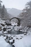Arch bridge in mountains during winter, South Alps, Italy. Ruins of arch bridge in mountains during winter, Rezzo municipality, Province of Imperia, Italy Royalty Free Stock Photo