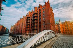 Arch bridge over canals in the Speicherstadt of Hamburg. Warm evening sun light on red brick building stock images