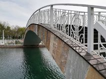 Arch bridge over the lake. Wooden arch bridge with white iron railing across the lake in the Park. the reflection in the water Stock Photo