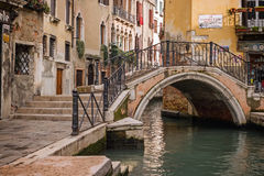 Arch bridge over a narrow canal in Venice. Arch bridge over a narrow canal in Venice, Italy Royalty Free Stock Image