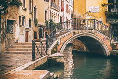 Arch bridge over a narrow canal in Venice, Italy. Retro photo of  arched bridge over a narrow canal in Venice, Italy Royalty Free Stock Images