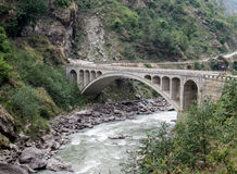 Arch Bridge over River. An arched bridge over the river in the valley Royalty Free Stock Photography